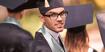 A male honors graduate during ceremony amid his peers.